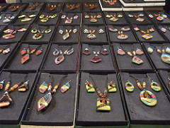 A display of handmade craft necklaces and earrings in different colors and designs