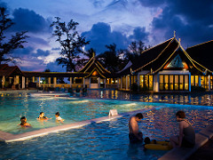A resort pool with guest swimming in a sunset sky view