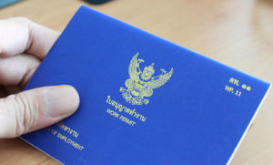 A hand holding Thailand's working permit visa in blue cover