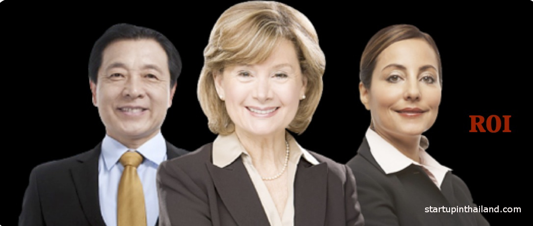 A blonded hair woman on the center together with an asian man on her right and another woman on left wearing business attire facing front