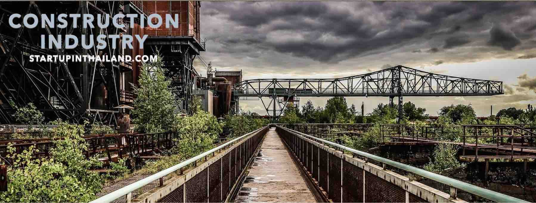 Iron bridge in a construction site with large crane in a dark clouds view