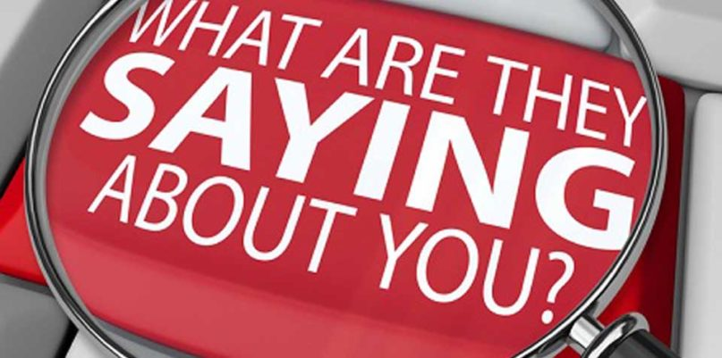 A magnifying glass on a key tab enlarging view of a text 'What are they saying about you' in red fill