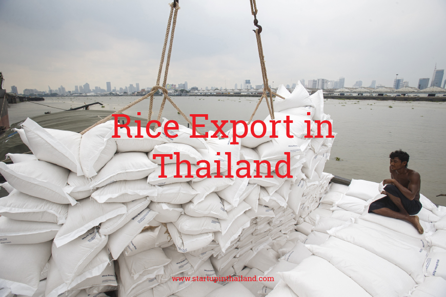 Thailand's port with tons of rice in white sack being lift by a crane while a laborer sat down in the corner watching