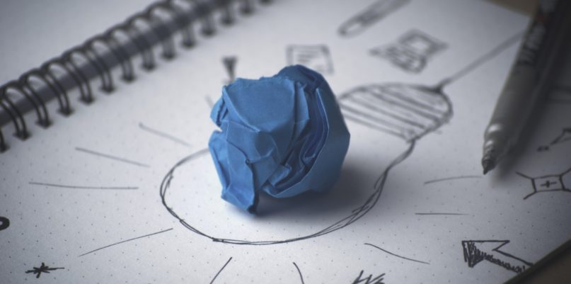 blue crampled paper on top of another paper